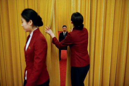 A security officer keeps watch behind a curtain on the second day of the 19th National Congress of the Communist Party of China at the Great Hall of the People in Beijing, October 19, 2017. REUTERS/Thomas Peter