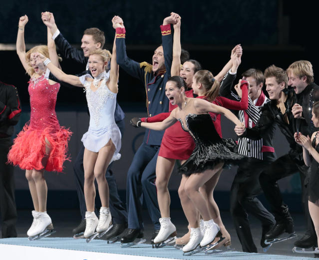 The Russian team wave to spectators as they stand on the podium during the flower ceremony after placing first in the team figure skating competition at the Iceberg Skating Palace during the 2014 Winter Olympics, Sunday, Feb. 9, 2014, in Sochi, Russia. (AP Photo/Ivan Sekretarev)