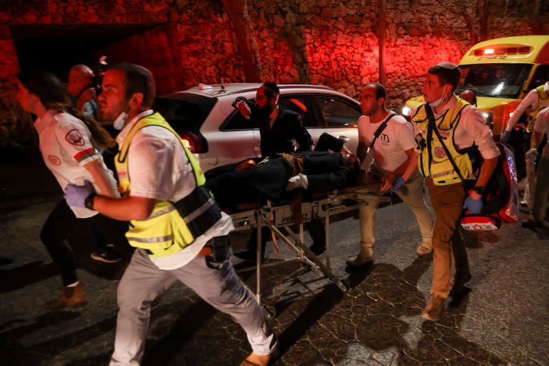 Rescue workers carry injured people outside a synagogue in Givat Zeev