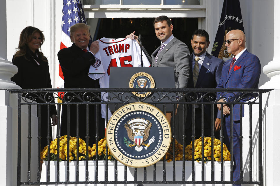 Washington Nationals first baseman Ryan Zimmerman, center, presents a jersey to President Donald Trump during an event to honor the 2019 World Series champion Nationals baseball team at the White House, Monday, Nov. 4, 2019, in Washington. Standing alongside are first lady Melania Trump, left, manager Dave Martinez, second from right, and general manager Mike Rizzo. (AP Photo/Patrick Semansky)