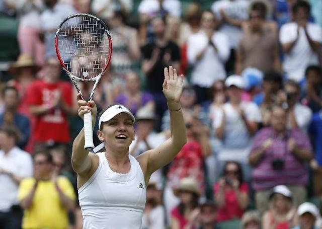 Simona Halep of Romania reacts to the applause of the crowd after defeating Sabine Lisicki of Germany in their women's singles quarterfinal match at the All England Lawn Tennis Championships in Wimbledon, London, Wednesday, July 2, 2014. (AP Photo/Pavel Golovkin)