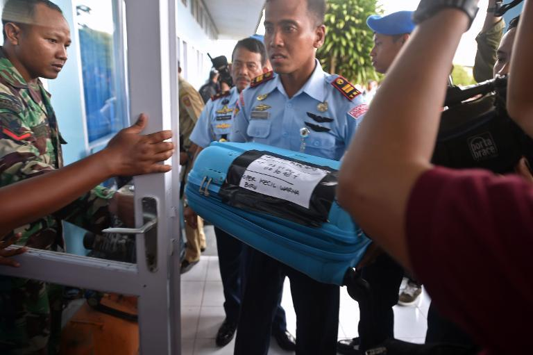 A member of the Indonesian air force carries an item retrieved from the Java Sea during search and rescue operations for the missing AirAsia flight QZ8501, in Pangkalan Bun, Central Kalimantan, on December 30, 2014