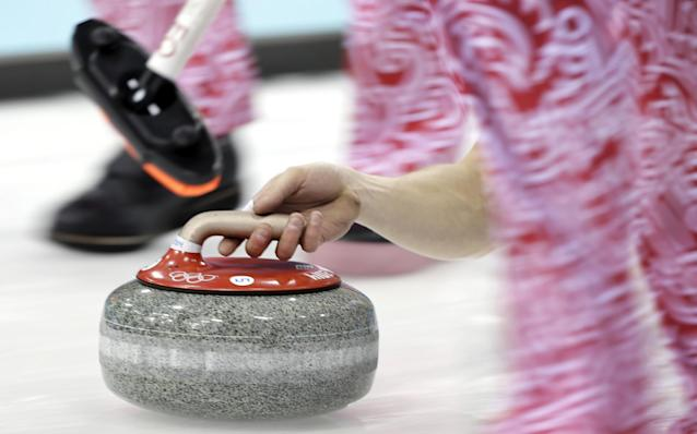 Russia's Evgeny Arkhipov delivers the rock during the men's curling competition against China at the 2014 Winter Olympics, Saturday, Feb. 15, 2014, in Sochi, Russia. (AP Photo/Wong Maye-E)