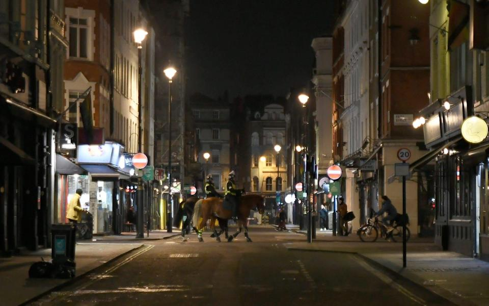 Two mounted police patrol the Soho area with its pubs shops restaurants and bars now closed  - Alberto Pezzali /AP