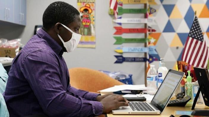 Teaching assistant Samuel Lavi helps out with an online class at the Valencia Newcomer School, Tuesday, Sept. 2, 2020, in Phoenix. Communicating during the coronavirus pandemic has been trying for parents and students at the Phoenix school for refugees who speak a variety of languages and are learning to use technology like iPads and messaging apps. (via AP/ Ross D. Franklin)