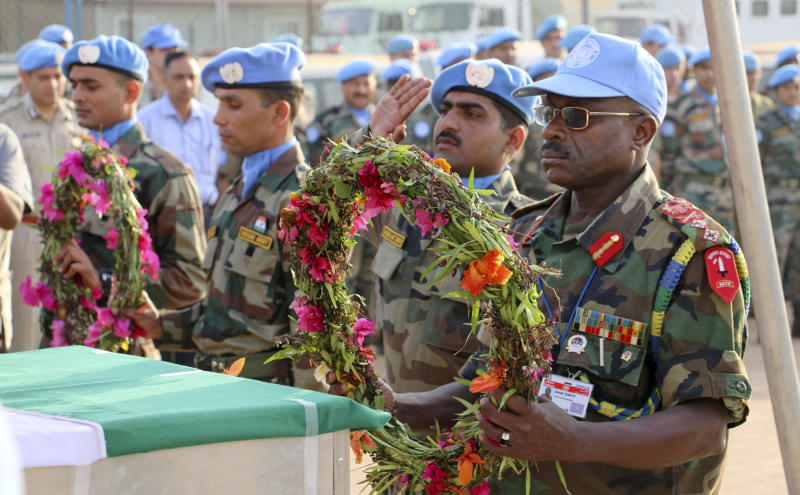 In this photo released by the United Nations Mission in South Sudan (UNMISS), Force Commander Maj. Gen. Delali Sakyi of Ghana prepares to lay flowers on the coffins of his two colleagues who were killed on Thursday, at a memorial service held in the UNMISS compound in Juba, South Sudan Saturday, Dec. 21, 2013. The U.N. peacekeeping mission strongly condemned the unprovoked attack on a U.N. base in Akobo in Jonglei state, near the Ethiopian border, on Thursday that killed two Indian peacekeepers and injured a third. (AP Photo/UNMISS)
