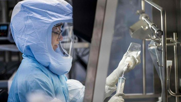 Employee in cleanroom suit at a laboratory workstation