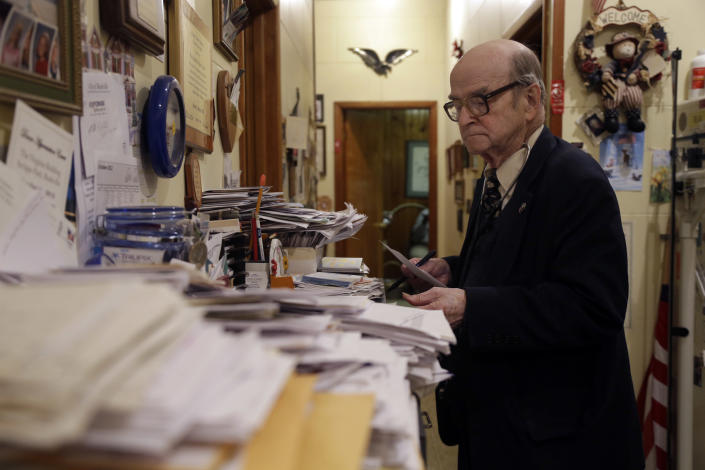 In this Tuesday, Oct. 30, 2012 photo, Dr. Russell Dohner looks over paper records between seeing patients in Rushville, Ill. His office has no fax machines, or computers, or other forms of modern technology. Medical records are kept on hand-written index cards, stuffed into row upon row of filing cabinets. (AP Photo/Jeff Roberson)