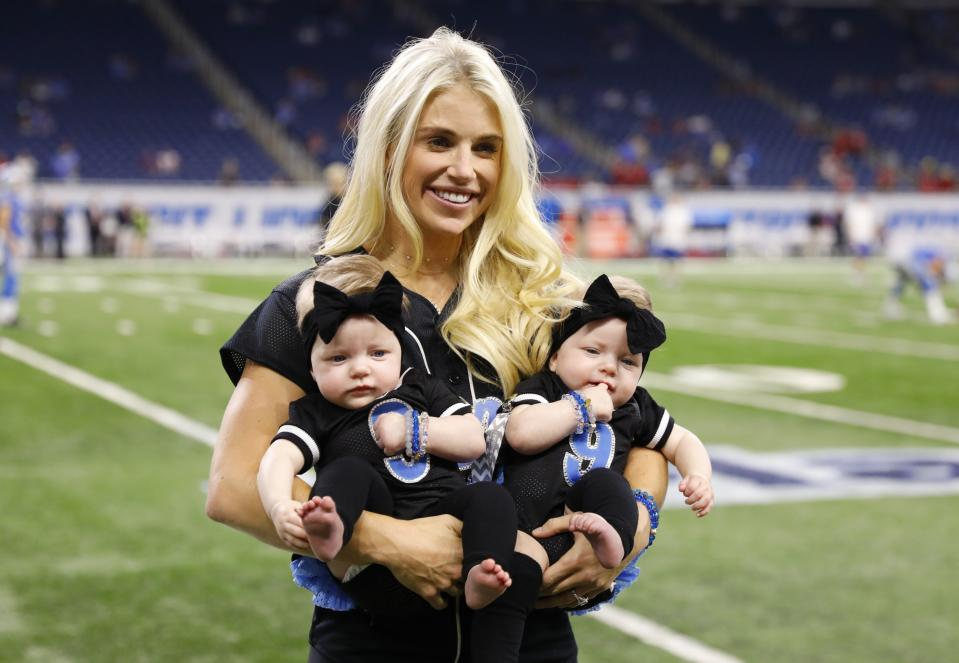 FILE - In this Sept. 24, 2017, file photo, Kelly Stafford, wife of Detroit Lions quarterback Matthew Stafford, holds the couple's twins Sawyer, left, and Chandler during pre-game of an NFL football game against the Atlanta Falcons, in Detroit. Kelly Stafford plans to have surgery to remove a brain tumor. Stafford shared the details Wednesday, April 3, 2019, on her Instagram account. She says an MRI showed the tumor on cranial nerves after she had vertigo spells within the last year. (AP Photo/Rick Osentoski, File)