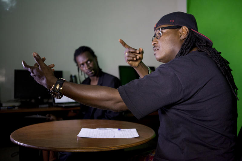 In this photo taken Tuesday, Sept. 10, 2013, guest commentator Senegalese rap icon Didier Awadi, right, lays down verse about the week's news as Makhtar 'Xuman' Fall looks on, during a taping of the 'Journal Rappe,' in Dakar, Senegal. In the span of a program just five minutes long, Fall and his co-host Cheikh 'Keyti' Sene tackle, in rhyming verse, everything from the Middle East to local woes like the flooding that disproportionately hits poor suburbs of Senegal's capital. The news and commentary show, rapped in French and Wolof, went viral on YouTube earlier this year and now airs twice a week on Senegalese television. (AP Photo/Jane Hahn)