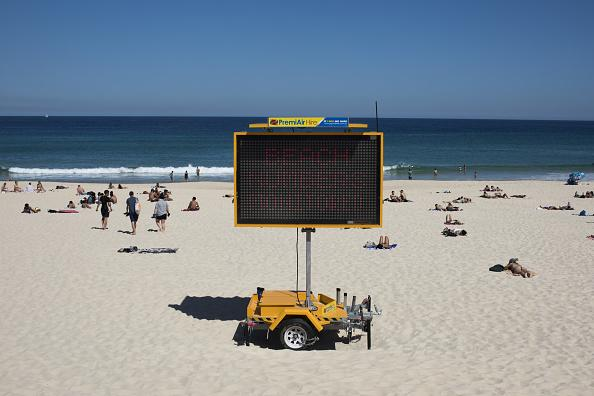 A sign reads 'Beach Numbers Monitored' at Bondi Beach in Sydney, Australia.