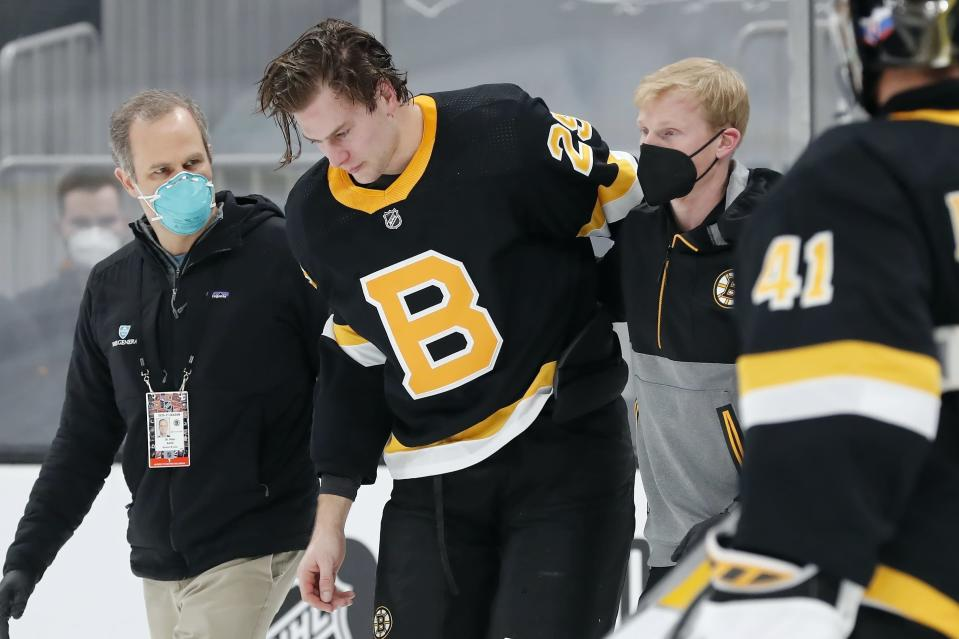 Boston Bruins' Brandon Carlo is helped off the ice after an injury in the first period of an NHL hockey game against the Washington Capitals, Friday, March 5, 2021, in Boston. (AP Photo/Michael Dwyer)