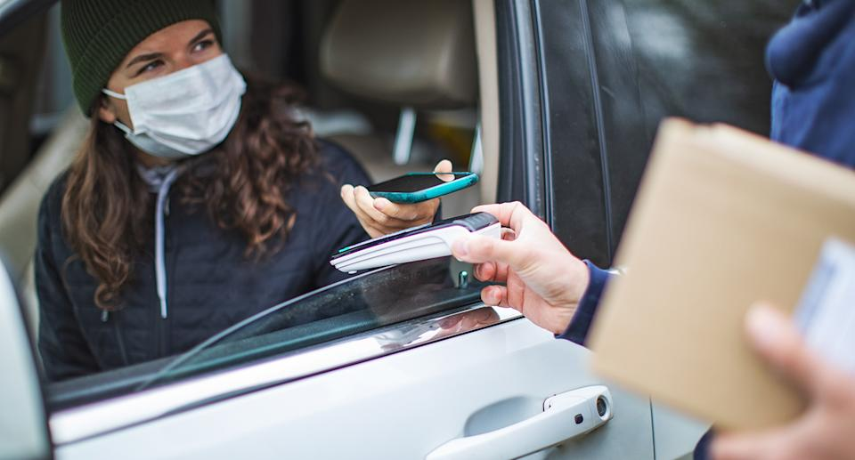 A woman pays for a food order with her phone through a car window. Source: Getty Images
