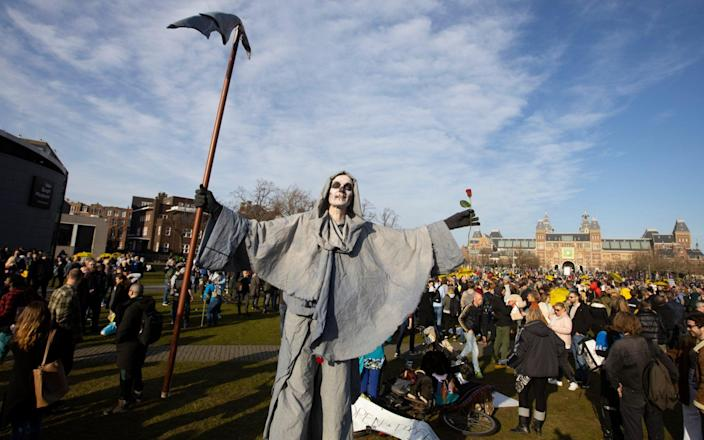 A person dressed as the grim reaper takes part in a demonstration of several hundreds of people against the lockdown and curfew in Amsterdam, - Peter Dejong/AP