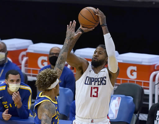 Los Angeles Clippers guard Paul George (13) takes a 3-point shot over Golden State Warriors forward Kelly Oubre Jr. during the second half of an NBA basketball game in San Francisco, Friday, Jan. 8, 2021. (AP Photo/Tony Avelar)