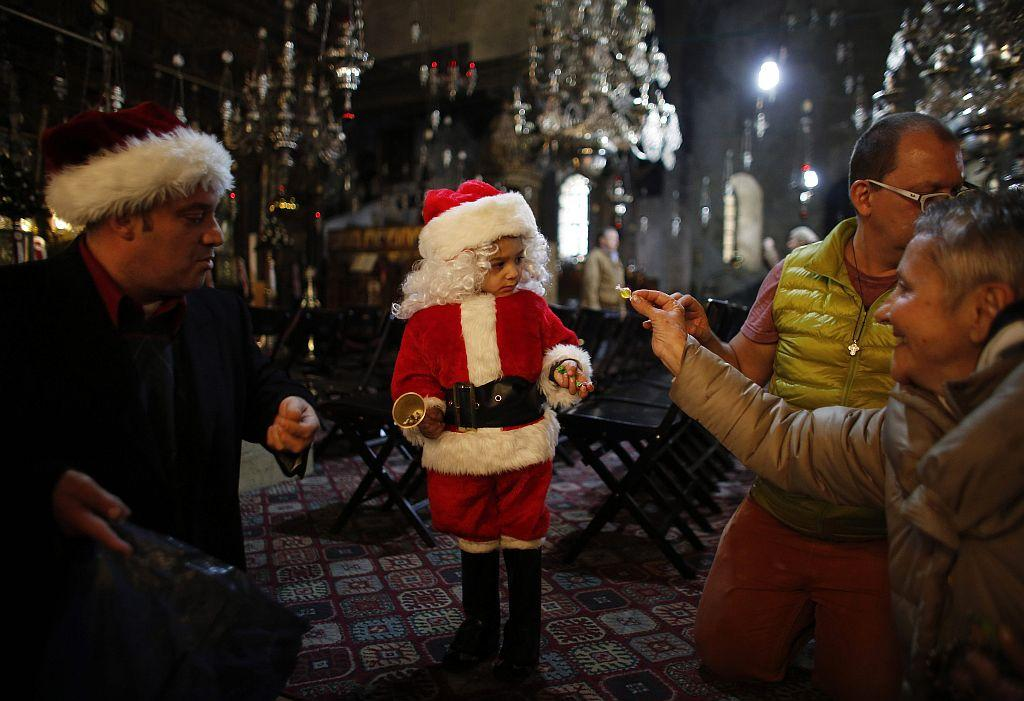 WEST BANK: A tourist offers a sweet to a boy dressed up as Santa Claus at the Church of the Nativity, the site revered as the birthplace of Jesus, in the West Bank town of Bethlehem January 6, 2013, during the Eastern Orthodox Christmas.