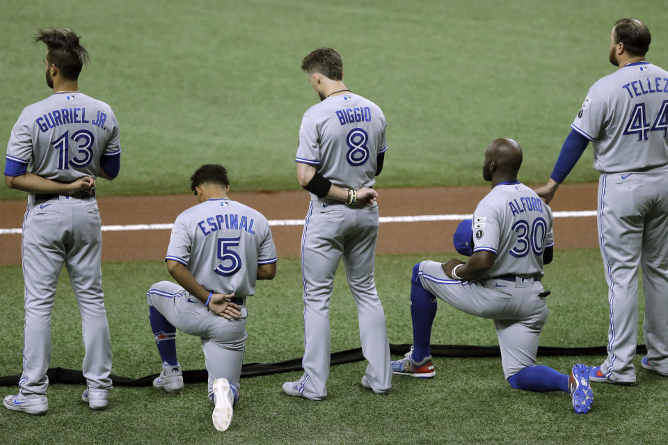 Lourdes Gurriel Jr., Cavan Biggio and Rowdy Tellez stand while Santiago Espinal and Anthony Alford kneel on the field during the U.S. national anthem.