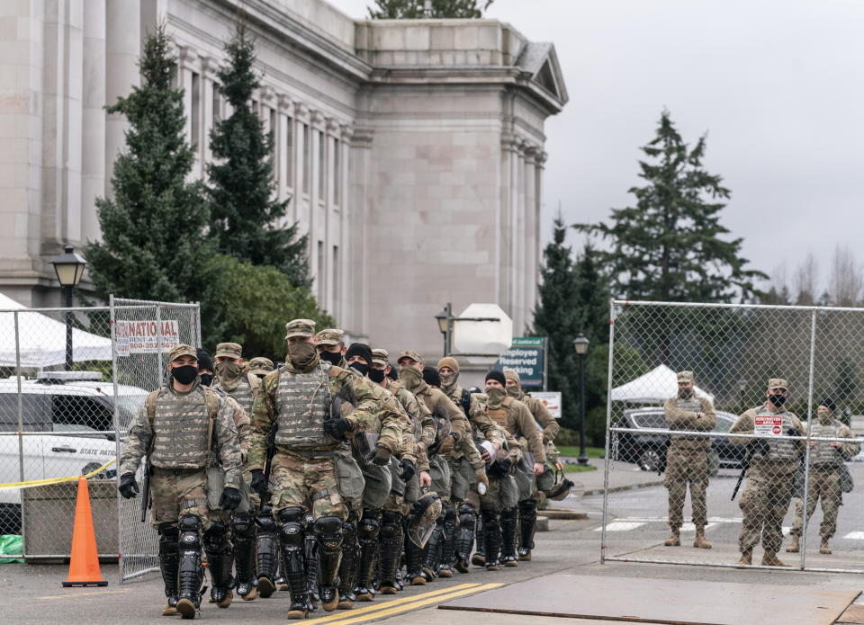 <p>Members of the National Guard leave the perimeter of the Washington State Capitol while providing extra security in Olympia, Washington, USA, 17 January 2021.</p> (EPA)