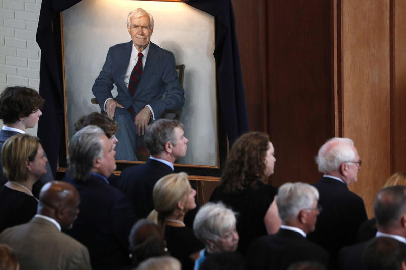A portrait of the late Republican senator Thad Cochran, looms over family members, during funeral services at Northminster Baptist Church in Jackson, Miss., Tuesday, June 4, 2019. Cochran was 81 when he died Thursday in a veterans' nursing home in Oxford, Mississippi. He was the 10th longest serving senator.
