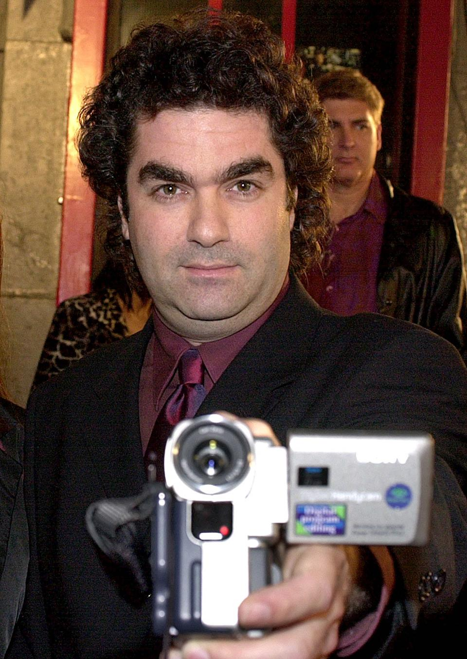 """Joe Berlinger films the media as he arrives at the premiere of """"Blair Witch 2"""", in Hollywood, 23 October 2000. (AFP Photo/Lucy Nicholson via Getty Images)"""