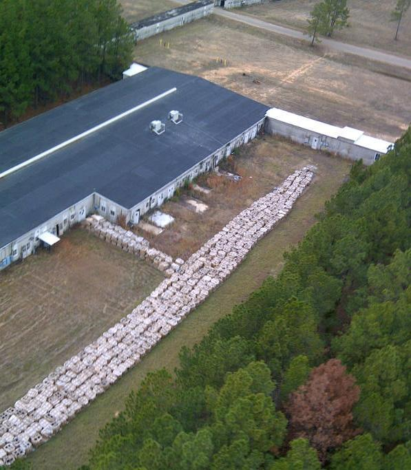 This aerial photo provided by the  Louisiana State Police shows part of the smokeless explosive powder improperly stored outside Explo Systems Inc., a munitions dismantling facility at Camp Minden at Doyline, La. Police moved millions of pounds of explosives Monday that had been haphazardly stashed in warehouses in Louisiana, prompting hundreds to evacuate from harm's way in case any of it exploded. About half the 800 residents in nearby Doyline, about 40 miles south of the Arkansas line, heeded state police warnings to evacuate until the stash could be divided into smaller quantities. (AP Photo/Louisiana State Police via The ( Shreveport ) Times)