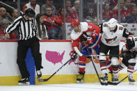 Washington Capitals left wing Alex Ovechkin (8), of Russia, and Arizona Coyotes left wing Lawson Crouse (67) battle for the puck next to the skate of linesman Travis Toomey (90) during the first period of an NHL hockey game, Monday, Nov. 11, 2019, in Washington. (AP Photo/Nick Wass)