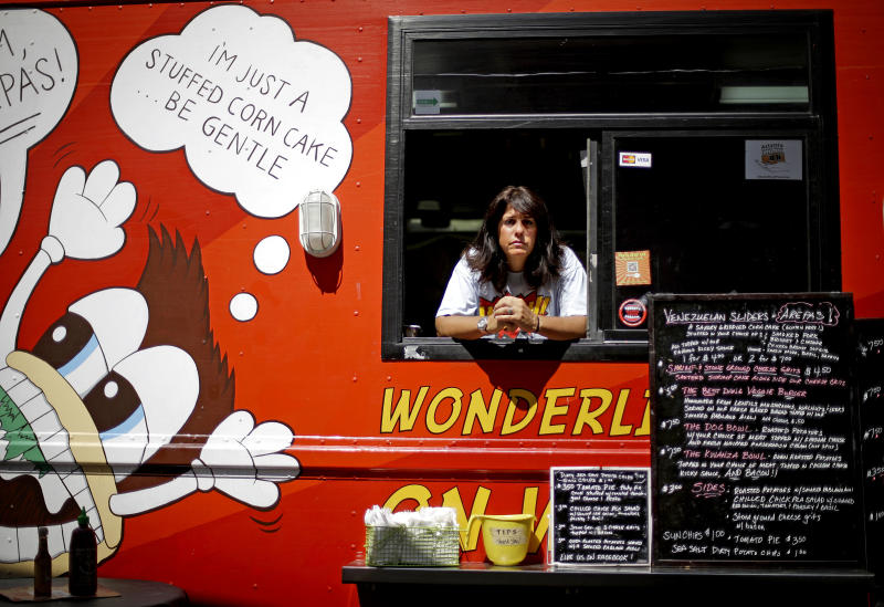 Wendy Cross looks out from her food truck as she waits for the lunch time crowd Tuesday, July 10, 2012, in Atlanta. After penning a rambling confession to financial regulators and writing notes to his family, south Georgia bank director Aubrey Lee Price boarded a ferry in Key West and disappeared. Now local and federal investigators are trying to determine whether Aubrey Lee Price killed himself or whether he slipped away with $17 million dollars of investors' money, including $300,000 of Cross'. Cross said she's shocked and devastated by the loss of her savings and is going to have to sell the truck because she needs the money to live.(AP Photo/David Goldman)