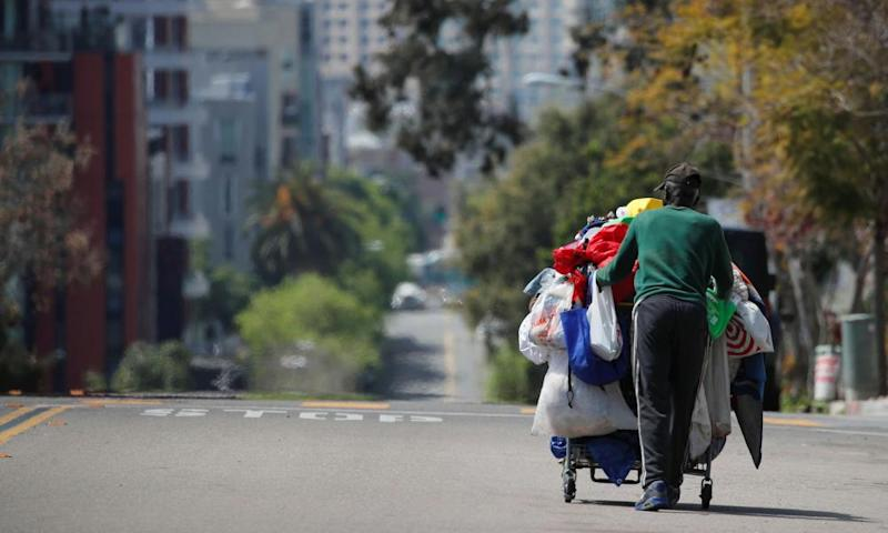 A homeless man pushes a cart full of his belongings along an empty street in San Diego. California has the largest homeless population in the US