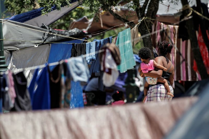 Asylum-seeking migrants, who were apprehended and returned to Mexico under Title 42 for crossing the border from Mexico into the U.S., are seen in a public square where hundreds of migrants live in tents, in Reynosa