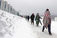 Migrants walk through the snow at the Lipa camp northwestern Bosnia, near the border with Croatia, Saturday, Dec. 26, 2020. Hundreds of migrants are stranded in a burnt-out squalid camp in Bosnia as heavy snow fell in the country and temperatures dropped during a winter spell of bad weather after fire earlier this week destroyed much of the camp near the town of Bihac that already was harshly criticized by international officials and aid groups as inadequate for housing refugees and migrants.(AP Photo/Kemal Softic)