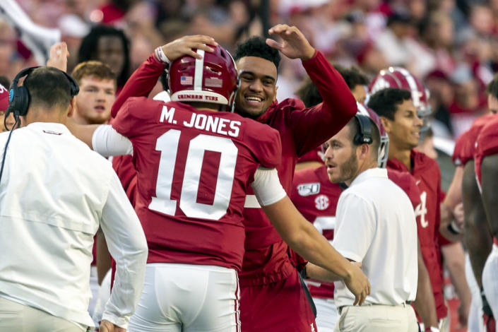 FILE - In this Oct. 26, 2019, file photo, Alabama quarterback Tua Tagovailoa, facing camera, out for the game due to injury, hugs quarterback Mac Jones (10), who is starting in Tagovailoa's place, at the start of the first half of an NCAA college football game against Arkansas in Tuscaloosa, Ala. The former Alabama teammates face each other when the Miami Dolphins and Tagovailoa, take on Jones and the New England Patriots on Sunday, Sept. 12, 2021, in Foxborough, Mass. (AP Photo/Vasha Hunt, File)