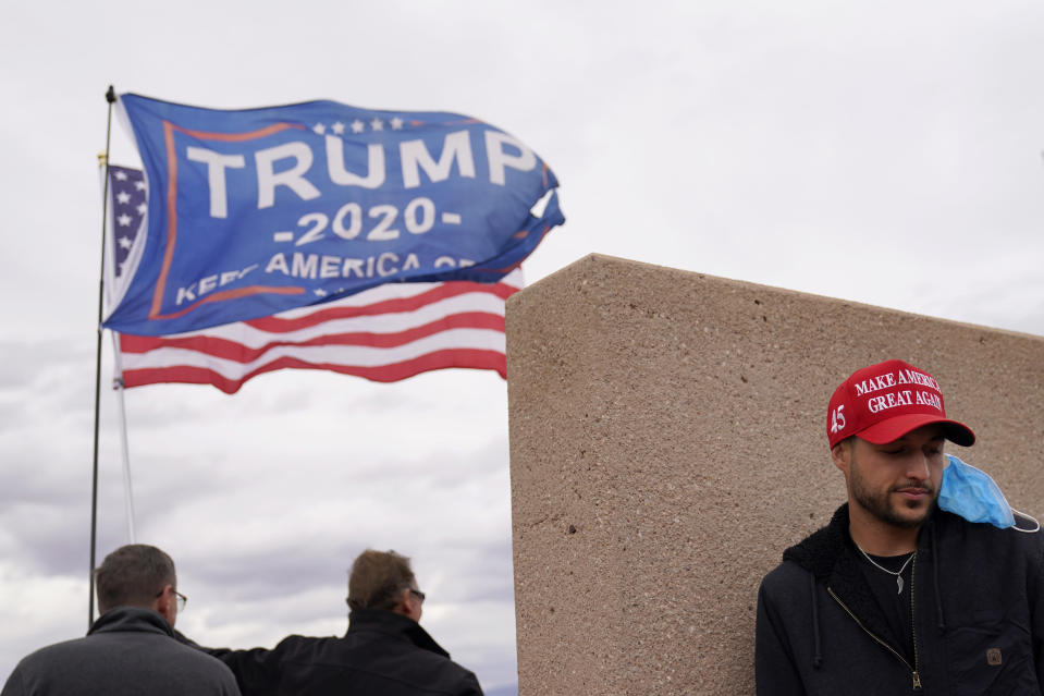 Supporters of President Donald Trump stand outside of the Clark County Elections Department in North Las Vegas, Nev., Saturday, Nov. 7, 2020. Democrat Joe Biden defeated President Donald Trump to become the 46th president of the United States on Saturday, positioning himself to lead a nation gripped by the historic pandemic and a confluence of economic and social turmoil. (AP Photo/John Locher)