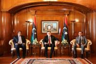 Libya's Prime Minister Abdulhamid Dbeibeh, Libya's internationally recognized former Prime Minister Fayez al-Sarraj, and Mohammed al-Menfi, Head of the Presidency Council, pose for a photo ahead of the handover ceremony in Tripoli