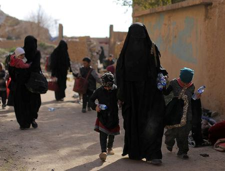 Families of Islamic state fighters walk as they surrendered in the village of Baghouz, Deir Al Zor province, Syria March 12, 2019. REUTERS/Rodi Said