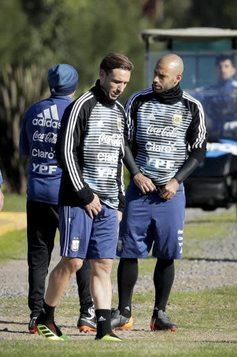 Javier Mascherano, right, talks with teammate Lucas Biglia during a training session with the Argentine national soccer squad in Buenos Aires, Argentina, Wednesday, May 23, 2018. Argentina will face Haiti on May 29 in an international friendly soccer match ahead of the FIFA Russia World Cup. (AP Photo/Victor R. Caivano)
