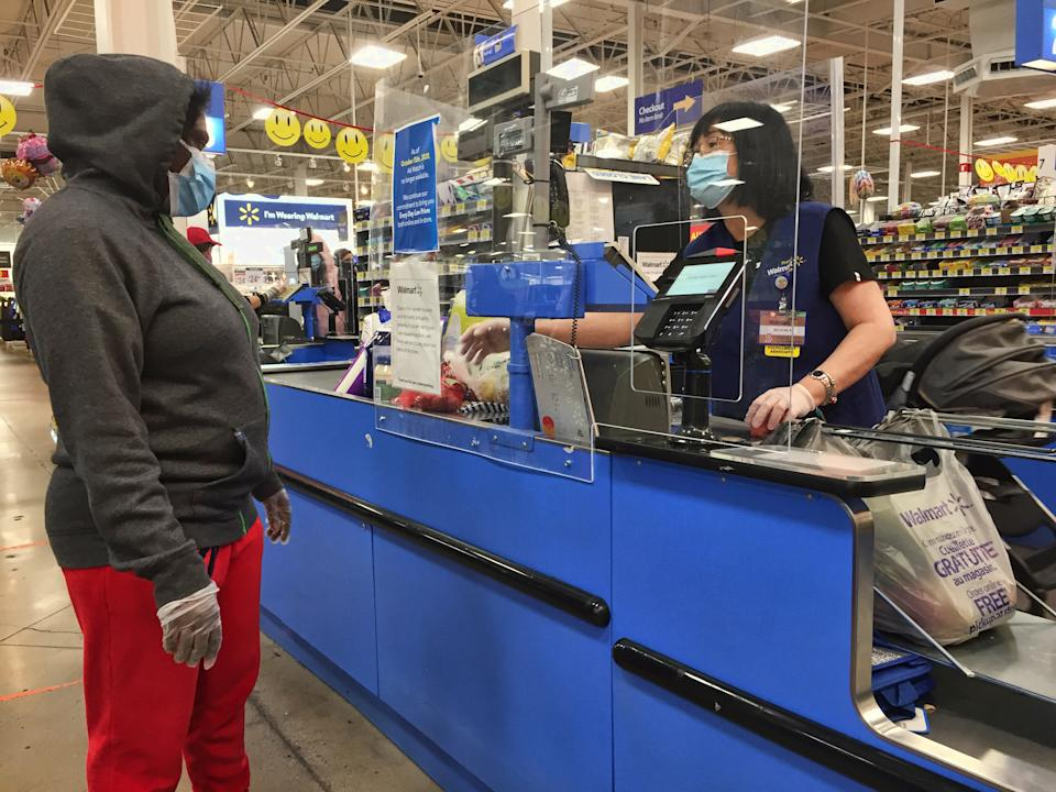 A cashier behind a plexiglass barrier to protect her from the coronavirus while helping a customer at a Walmart store in Toronto, Canada on October 20, 2020. (Photo by Creative Touch Imaging Ltd./NurPhoto via Getty Images)