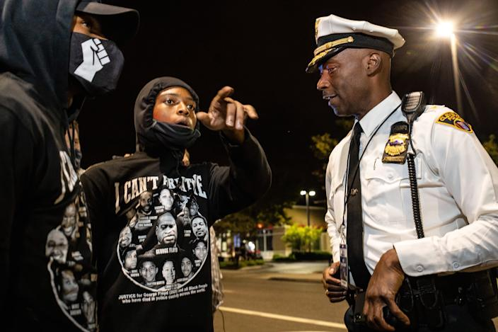 A police officer talks with protesters in front of the police barricade during the protest. (Stephen Zenner/SOPA Images/LightRocket via Getty Images)