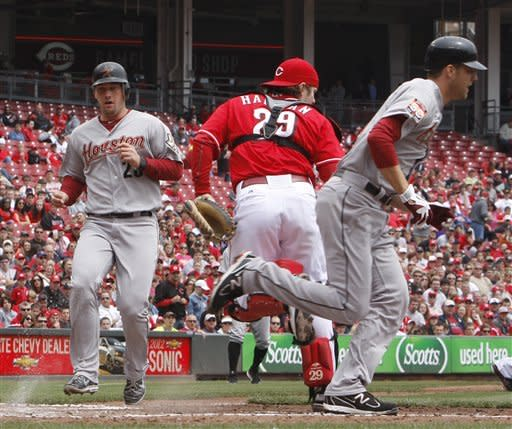 Houston Astros' Jordan Lyles, right, bunts as teammate Chris Johnson, left, scores during the second inning of a baseball game against the Cincinnati Reds, Sunday, April 29, 2012, in Cincinnati. Reds catcher Ryan Hanigan, center, awaits the throw. (AP Photo/David Kohl)