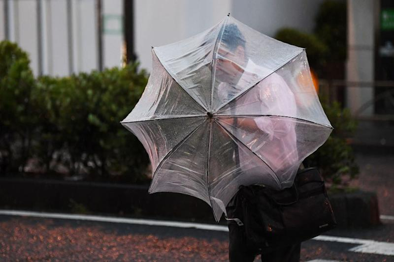 A man with an umbrella crosses a street early morning under the rain as a typhoon hits Tokyo on Sept. 9, 2019.