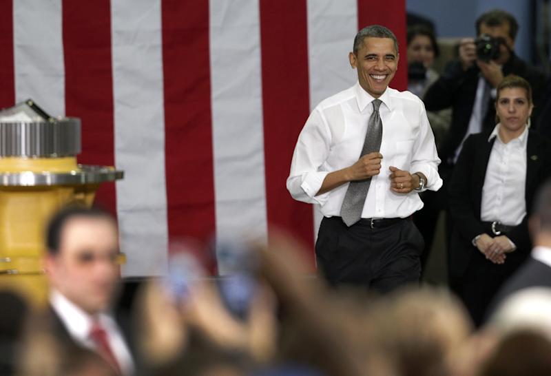 President Barack Obama runs to the stage before speaking to workers and guests at the Linamar Corporation plant in Arden, N.C., Wednesday, Feb. 13, 2013, as he travels after delivering his State of the Union address Tuesday. (AP Photo/Chuck Burton)