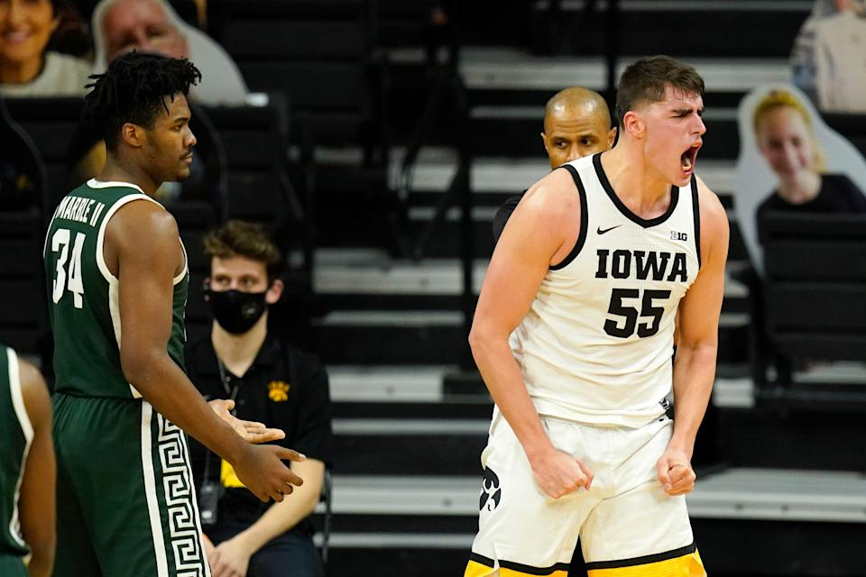 Iowa center Luka Garza celebrate in front of Michigan State forward Julius Marble II, left, after making a basket during the first half on Tuesday, Feb. 2, 2021, in Iowa City, Iowa.