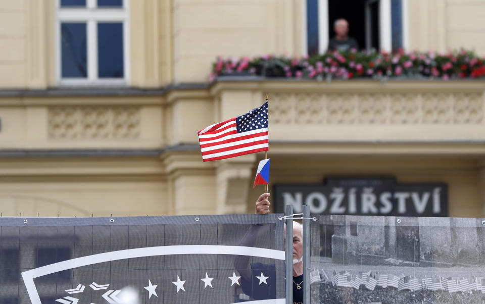 A man holds a flag as he stands behind a security fence during a ceremony with U.S. Secretary of State Mike Pompeo at the General Patton memorial in Pilsen near Prague, Czech Republic, Tuesday, Aug. 11, 2020. U.S. Secretary of State Mike Pompeo is in Czech Republic at the start of a four-nation tour of Europe. Slovenia, Austria and Poland are the other stations of the trip. (AP Photo/Petr David Josek, Pool)