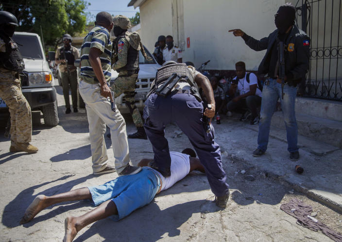 An inmate is recaptured outside the Croix-des-Bouquets Civil Prison after an attempted breakout, in Port-au-Prince, Haiti, Thursday, Feb. 25, 2021. At least seven people were killed and one injured on Thursday after eyewitnesses told The Associated Press that several inmates tried to escape from a prison in Haiti's capital. (AP Photo/Dieu Nalio Chery).