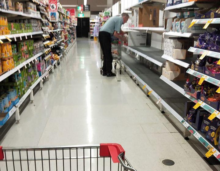 An elderly man searches a Coles aisle in Perth for toilet paper.