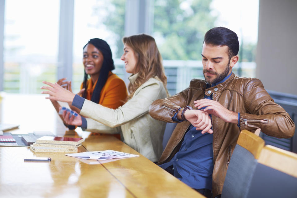 Pictured: Man checks his watch in boring meeting. Image: Getty