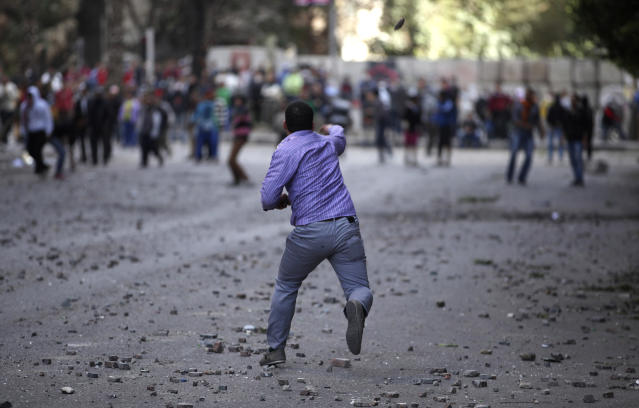 Pro and anti-government protesters throw stones during clashes near Tahrir Square in Cairo, Egypt, Wednesday, Jan. 30, 2013. Egypt's liberal opposition leader called for a broad national dialogue with the Islamist government, all political factions and the powerful military on Wednesday, aimed at stopping the country's eruption of political violence that has left scores dead in the past week. (AP Photo/Khalil Hamra)