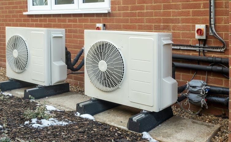 Two heat pump units with large fans installed on the outside of a house.