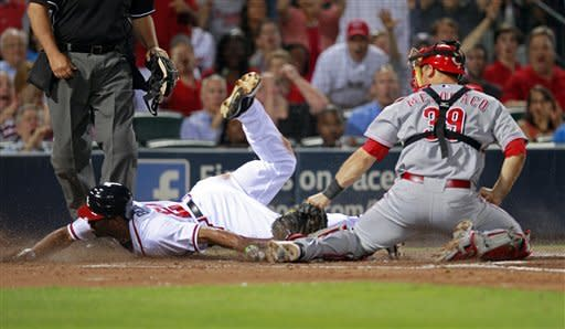 Atlanta Braves' Michael Bourn (24) scores on a Martin Prado sacrifice fly as Cincinnati Reds catcher Devin Mesoraco (39) makes the late tag in the fifth inning of a baseball game, Monday, May 14, 2012, in Atlanta. (AP Photo/John Bazemore)