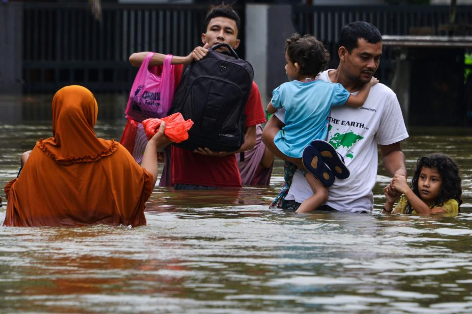 <strong>Floods in Indonesia: </strong>Floods ravaged Indonesia earlier this month, killing many and rendering many others homeless. A man and his children wade through floodwaters following three days of heavy rain in Banda Aceh on May 9, 2020.