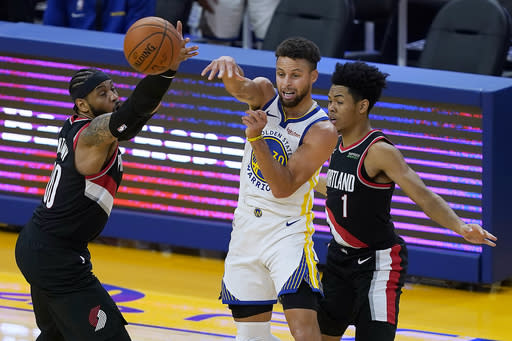 Golden State Warriors guard Stephen Curry (30) passes the ball between Portland Trail Blazers forward Carmelo Anthony (00) and guard Anfernee Simons (1) during the first half of an NBA basketball game in San Francisco, Friday, Jan. 1, 2021. (AP Photo/Tony Avelar)